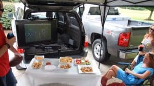 People watching a football match on TV at a tailgate party
