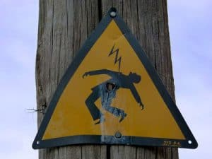 electric shock sign on a wooden post