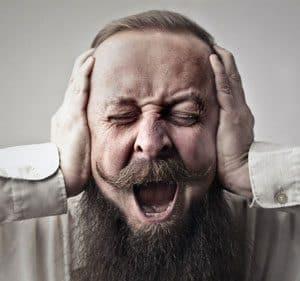 Screaming bearded man closing his ears